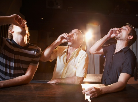 Group of men drinking alcohol shots