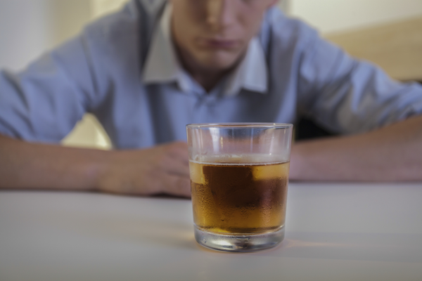 Man staring at liquor drink